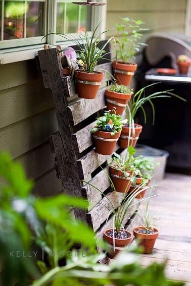 mur-vegetal-extérieur-palette-bois-avec-pots-de-fleur-suspendus deco cool